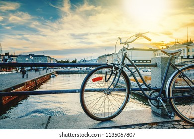 Black retro bicycle parked on the waterfront of Helsinki, the capital of Finland, against the backdrop of the city and sunset