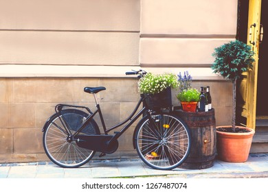 Black retro bicycle stands next to the barrel, flower pots, wine bottles, on the street, next to the open vintage door, against the background of a stone wall, with a free space for text.