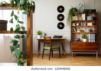 Black retro typewriter on a unique wooden desk, a mid-century modern chair and a renovated bookcase in a hipster home office interior. Real photo.