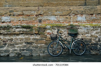 Black retro vintage bicycle with basket on old brick wall, with copy space