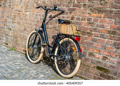 Black retro vintage bicycle with old brick wall. Retro bicycle with basket in front of the old brick wall. Retro bicycle on roadside with vintage brick wall background.