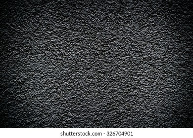 Black revetment wall putty high contrasted with vignetting effect macro texture background