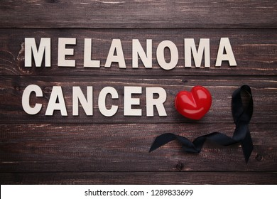 Black ribbon with red heart. Melanoma concept