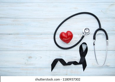 Black ribbon with red heart and stethoscope. Melanoma concept
