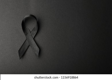 Black ribbon and space for text on dark background, top view. Funeral accessory