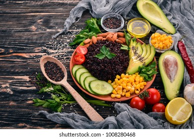 Black Rice Avocado Cucumber Corn And Almonds On A Wooden Background