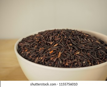 black rice in ceramic cup with wooden spoon