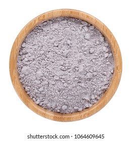Black rice flour powder in wooden bowl isolated on white. Top view.