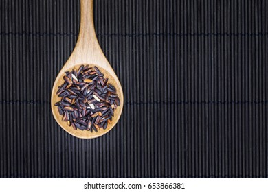 Black rice on the black bamboo mat background
