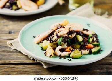 Black rice with prawns, vegetables and orange, selective focus
