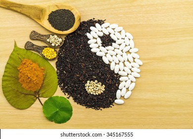 Black rice and white pill  forming a yin yang symbol  and Spa herbal compressing ball , turmeric powder , millet , soybean , basil seed in wooden spoon  on brown wooden  blending of herb and medicine
