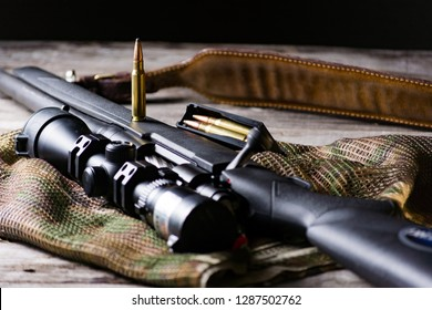 The Black Rifle with ammo and scope on the multicam background. Close up.
