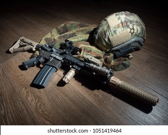 The Black Rifle with sound suppressor and tactical bulletproof helmet on the floor