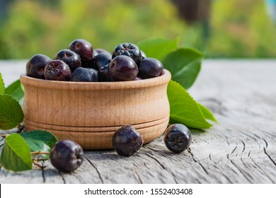 Black ripe berries of food, medicinal shrub Aronia, chokeberry (Aronia melanocarpa) in a wooden plate on an old wooden table, rustic style, close-up, healthy food concept, copy of space