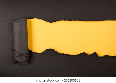 Black ripped piece of paper, space for copy on yellow background
