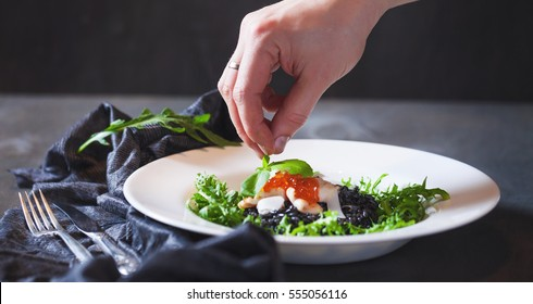 Black risotto with arugula, Parmesan cheese in a red caviar.