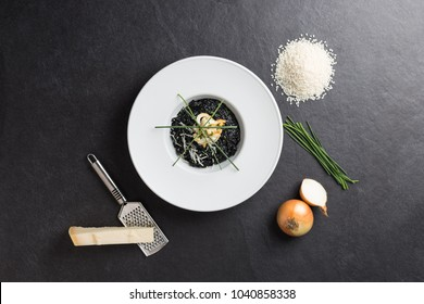 Black risotto cuttlefish served on white plate on black table