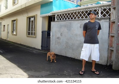 Black River, Mauritius. July 2010. Young mauritian man proudly posing with dog in front of his home.
