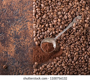 Black roasted coffee grains and ground coffee in spoon lie on a copper table, background image, top view, copy space for your text.