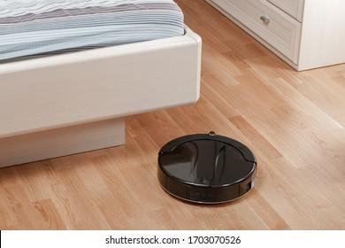 black robotic vacuum cleaner runs on laminate floor under bed in bedroom. Modern smart cleaning technology housekeeping.