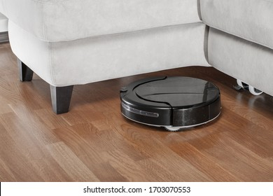 black Robotic vacuum cleaner runs under sofa. Robot controlled by voice commands to direct cleaning. Modern smart cleaning technology housekeeping.