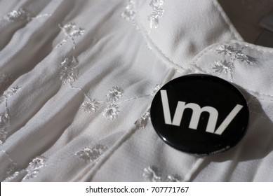 Black rock knuckle button pin on an embroidered white blouse