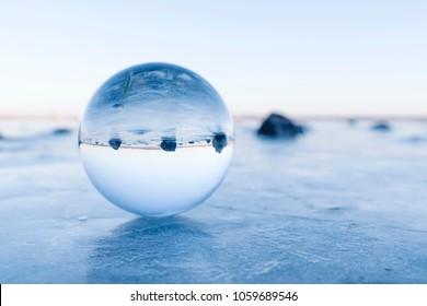 Black rocks in a glass orb on a frozen lake in the winter