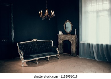 Black room in the castle with a window, a chandelier, part of the door  and sofa and mirror and fireplace. Space where you can put a person.