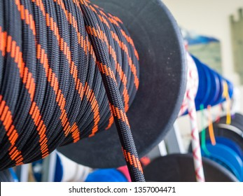 Black rope on a show-window of shop. A saving rope for climbers. The rope is reeled up on the coil. Texture of a rope