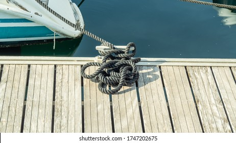 Black rope tied to the bollard and white Board berth