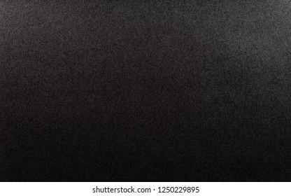 Black, rough textured background lit with dim light.
