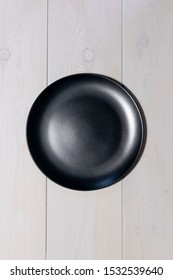 a black round empty plate stands on a gently gray wood background with a wood texture.  the view from the top.