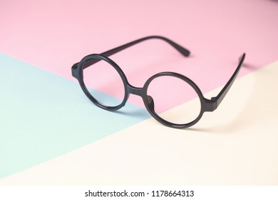 black round glasses on pale pink blue yellow bacground minimalism concept