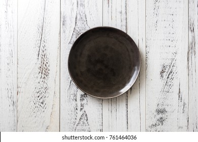 Black Round Plate on white wooden table background