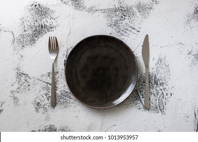 Black Round Plate with utensils on white scraped wooden table background