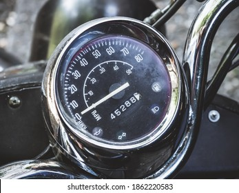 Black round speedometer with an arrow located on the handlebars of the motorcycle. Closeup photo