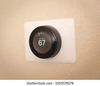 """Black, round thermostat with digital screen reading """"Heat Set To 67""""."""