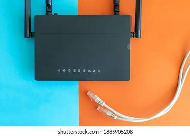 a black router on a bright two-color background, a cable stretches towards it from below