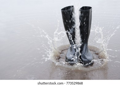 Black rubber boots fall into a puddle and the water splashes. Wellies are fashionable and the right footwear for bad weather. Rubber boots become art.