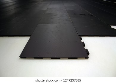 Black rubber floor covering on a gray background. Puzzles to cover the ice.