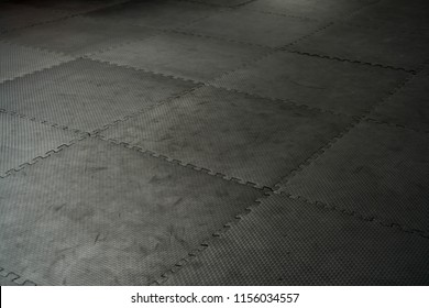 Black rubber floor mat and tiles inside a gym. Black rubber fitness floor texture and background.safety mats reduce the injury risk caused by falls on playgrounds and sport facilities.