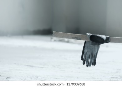 Black rubber gloves on wooden stick in construction site.