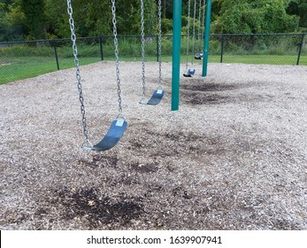 black rubber swing seats with swingset and wood chips