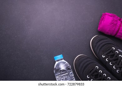 Black Running / Sneaker shoe, water bottle and towel on black stone floor. Exercise concept. Top view