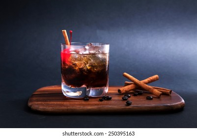 Black Russian Cocktail  made with vodka, coffee liqueur and cream. Coffee beans garnish and cinnamon stick and red cherry on  wooden cutting board