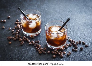 Black Russian Cocktail with Vodka and Coffee Liquor. Homemade Alcoholic Boozy Black Russian drink on black background with copy space.