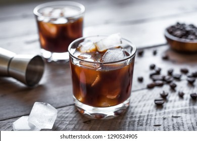 Black Russian Cocktail with Vodka and Coffee Liquor. Homemade Alcohol Boozy Black Russian drink with coffee beans on wooden background with copy space.