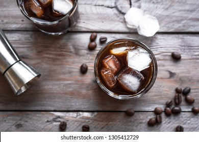 Black Russian Cocktail with Vodka and Coffee Liquor. Homemade Alcohol Boozy Black Russian drink with coffee beans on wooden background.