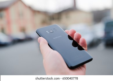 A black Samsung Galaxy S8 smartphone is showed off at press event in Riga - March 29, 2017. Shallow focus effect.