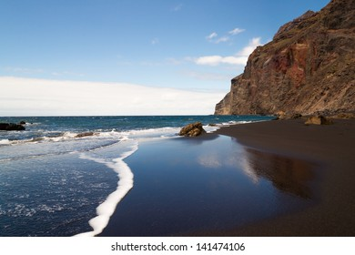 A black sand beach at the atlantic ocean at La Gomera, one of the canary islands. The sky is mirrored in the wet sand.